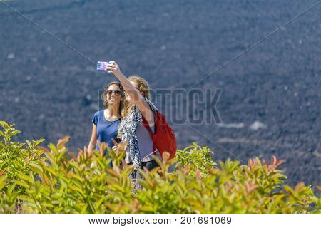 GALAPAGOS, ECUADOR, AUGUST - 2016 - Attractive young women taking a selfie at sierra negra volcano the second largest volcano on earth located in Isabela island Galapagos Ecuador
