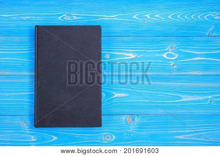 Old Black Book On Wooden Plank Background. Blank Empty Cover For Design