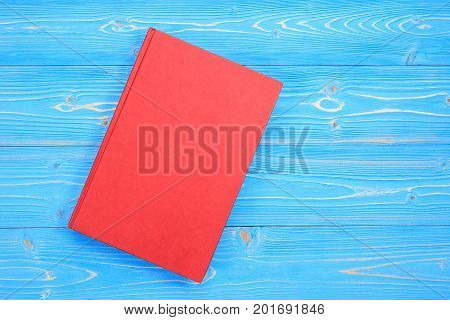 Old Red Book On Wooden Plank Background. Blank Empty Cover For Design