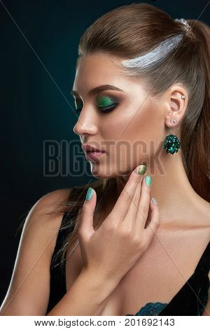 Beautiful brunette girl with hairstyle with elements of silver and green shiny makeup and manicure posing at studio. Woman with big rounded earring, looking down, touching face hand. Dark background.