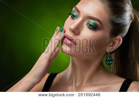 Studio portrait of sensual beautiful woman with shiny green makeup touching perfect bronze skin of face and plump lips. Brunette woman wearing in black top, big rounded earring posing at studio.