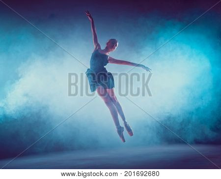The young ballet dancer jumping on a lilac background. Ballerina is wearing in blue dress and pointe shoes. The outline shooting - silhouette of girl with smoke effect