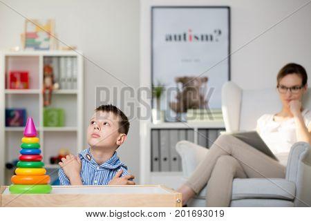 Pedagogue Sits On Grey Armchair