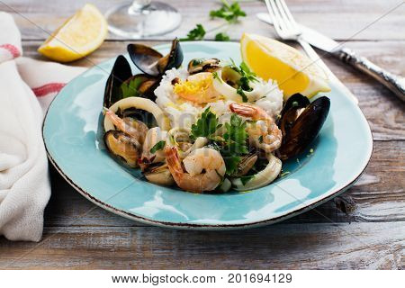 Seafood saute with rice on blue plate. Copy space