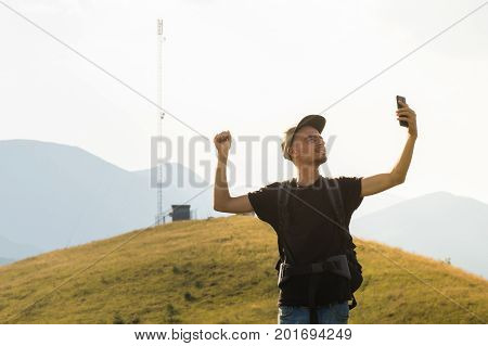 Male tourist on hiking trip happy to receive mobile network connection. Young person spending vacation in mountains holding cell phone near the cell network tower