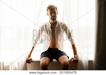 Young man in white unbuttoned shirt sits on windowsill against window.