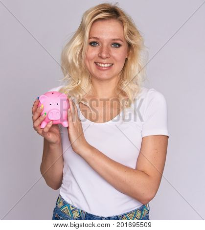 Happy Woman With Freckles Holds A Piggy Bank