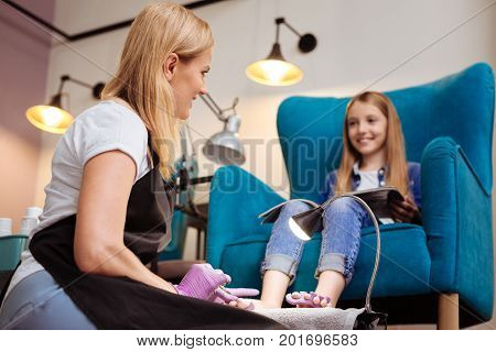 Pleasant chat. Pleasant young pedicurist removing the cuticle from toenails and talking to her client while the girl holding a magazine in her lap