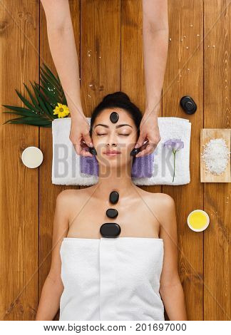 Black marble stone face massage in spa, top view. Female patient in wellness center. Professional massagist make relaxation procedure to beautiful indian girl in beauty parlor
