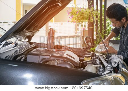 The technician is pouring clean water on the car's radiator Automotive industry and garage concepts.
