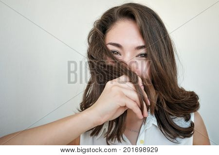 Shy girl hiding her face with hair. Beautiful eyes looking at camera