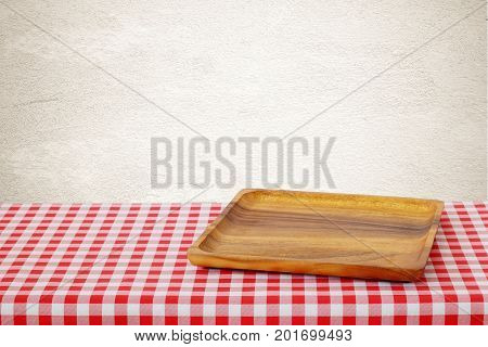 Empty wooden tray on red checked tablecloth over brown cement wall background kitchen utensil food display montage