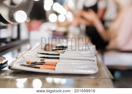 Best quality of equipment. The close up of a professional makeup brushes set lying on the table in a beauty salon while a makeup artist talking to her client in the background
