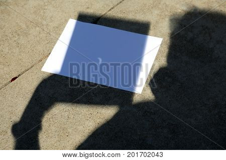 Solar Eclipse 2017. A man uses a pin hole in a sheet of paper to photograph the Solar Eclipse on September 21, 2017. Shadow with solar eclipse example