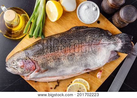 Trout spent raw on a cutting wooden board with spices, herbs, salt, lemon and olive oil