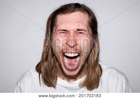Angry screaming adult man on gray backdrop. Rage emotion background. Evil young male shouting, furious feelings, conflict person