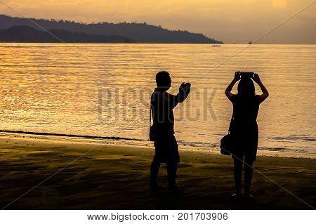 Kota Kinabalu,Sabah-Aug 8,2017:Silhouette of people taking photo with smart phone camera enjoying sunset scenery at Kota Kinabalu beach,Sabah.Smart phone camera are getting better all the time at taking photos with big megapixel.