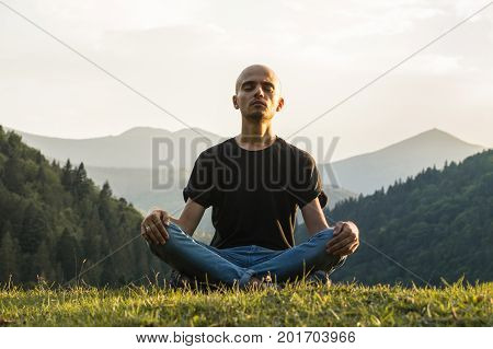Young man does yoga in mountains at sunset. Skinny male person sits in lotus position top of the hill in ukrainian carpathian mountains