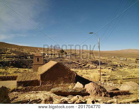 An ancient clay church located at Socaire, nearby the Atacama Desert, Chile, and a volcano on the background