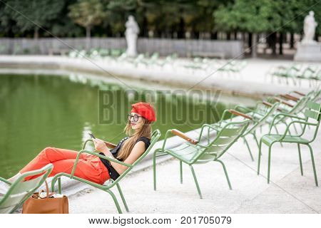 Young stylish woman in red cap and pants sitting on the famous green chairs in Tuileries garden in Paris