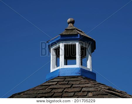 The freshly painted cupola atop a roof of weathered wooden shingles harmonizes with the deep blue sky.