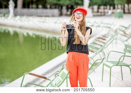 Young stylish woman tourist in red cap and pants standing with photocamera near the famous green chairs in Tuileries garden in Paris