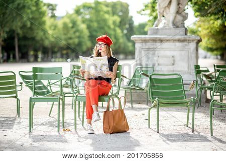 Young stylish woman tourist in red cap and pants sitting with paper map on the famous green chairs in Tuileries garden in Paris