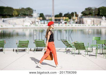 Young woman in red walking in Tuileries park in Paris
