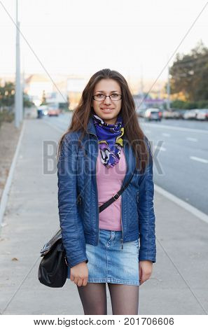 Cheerful brunette girl in casual clothes walking through street