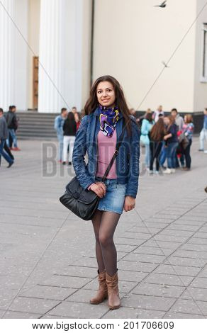 Cheerful young brunette girl in casual clothes walking through street