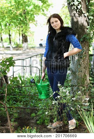 Happy casual dressed woman in yard gardening with flowers