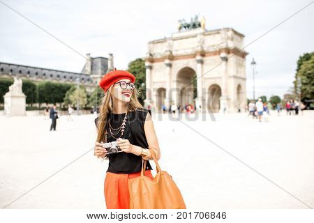Young woman tourist in red cap standing with photo camera in front of the triumphal arch at the Tuileries park in Paris
