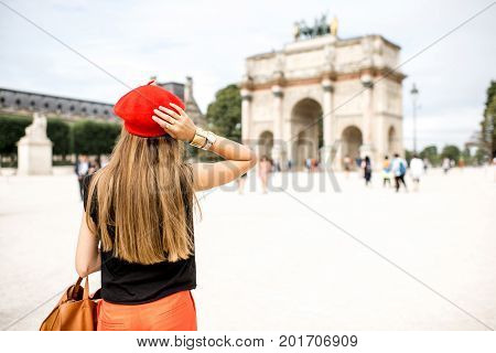 Young woman tourist in red cap standing back in front of the triumphal arch at the Tuileries park in Paris