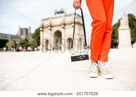 Woman tourist in red pants standing with photo camera in front of the triumphal arch at the Tuileries park in Paris