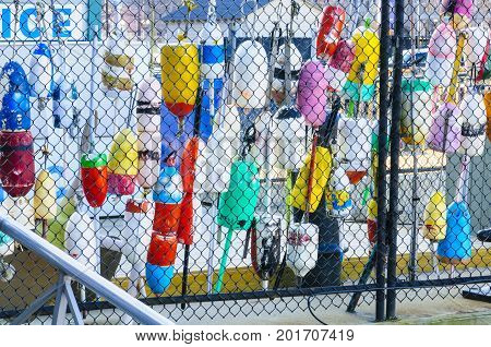 Colorful fishing gear resting against chain link fence