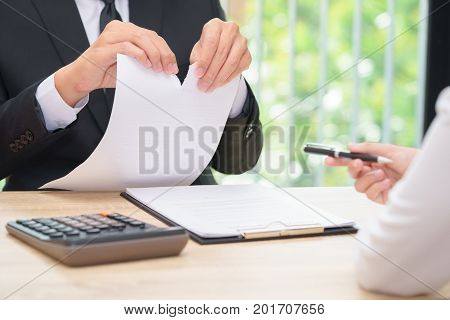 Hands of businessman ripping agreement paper when woman giving a pen for signing break the rules - failure business concept