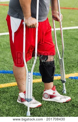 An injured player is on the sidelines wearing a knee brace and using crutches after he has had knee surgery.