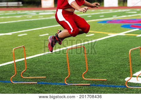 A football player is jumping over orange hurdles on a green turf field during high school practice on a warm August night.