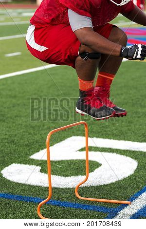 A lineman jumps over hurdles at football practice on a green turf field