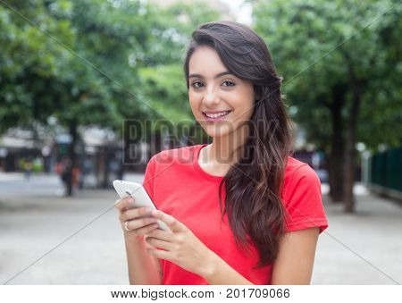 Laughing girl with red shirt surfing the net with phone outdoor in the city in the summer