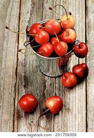 Arrangement of Ripe Sweet Maraschino Cherries in Tin Buckets closeup on Rustic Wooden background