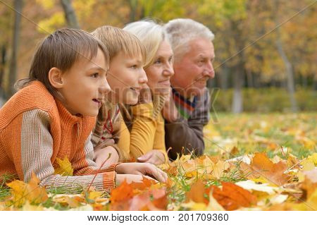 Grandparents and grandchildren together in autumn park