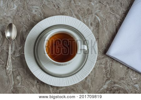 Tea table set for one person: cup, two plates, spoon and white tissue napkin. It's all served for breakfast in the morning on a gray marble countertop