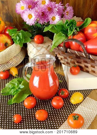 Tomato juice in a glass jug surrounded by tomatoes and green on a wooden background