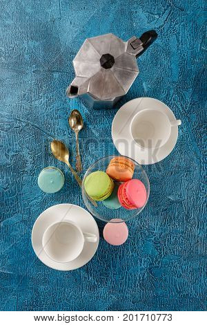 Classic French colorful mackerel cookies in glass vase cups for coffee and metal coffee maker on blue background