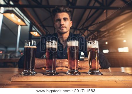 Young Man Tasting Different Varieties Of Craft Beer