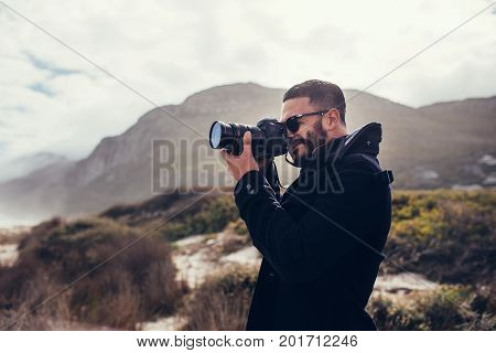 Handsome man with digital camera outdoors. Young male photographer photographing in nature on winter day.
