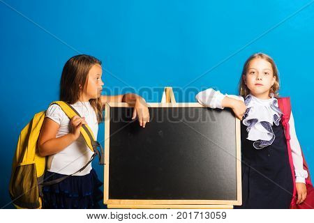 Schoolgirls With Serious Faces Stand Near The Blackboard