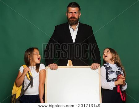 Man with beard and serious face stands near children with big schoolbags copy space. Girls in school uniform on green background. Schoolgirls stand next to blackboard. Education and school concept