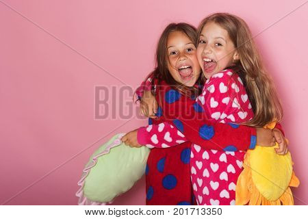 Girls In Colorful Polka Dotted Pajamas Hold Funny Pillows